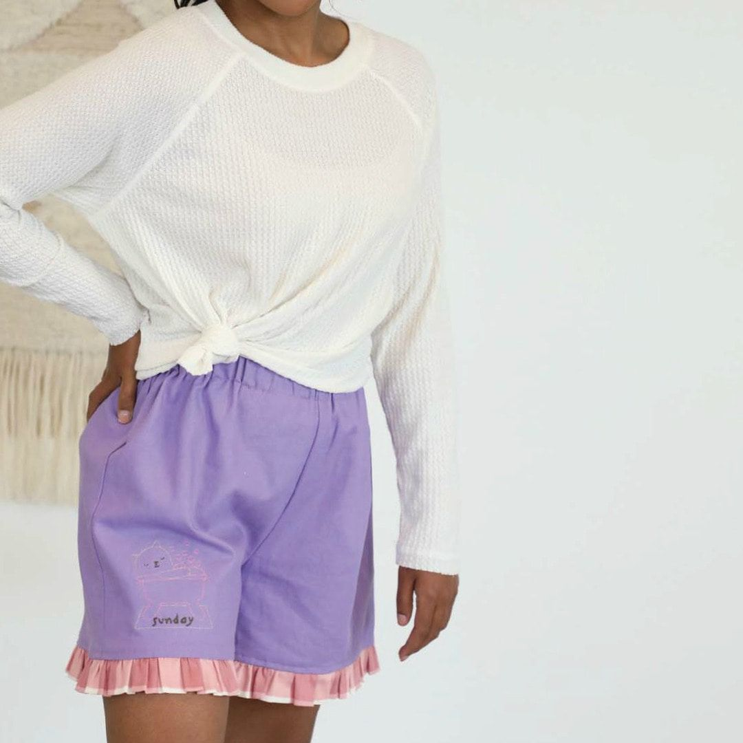 """A model wears a pair of purple shorts with pink ruffled trim, embroidered with a lazy cat with the word """"Sunday."""""""