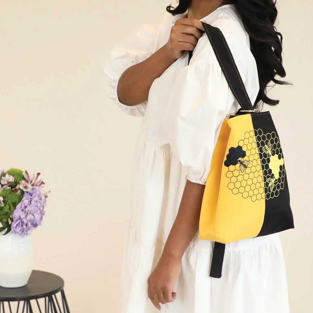 Model showing a small handmade backpack, half yellow and half black, with a honeycomb and bee embroidery motif on the center.