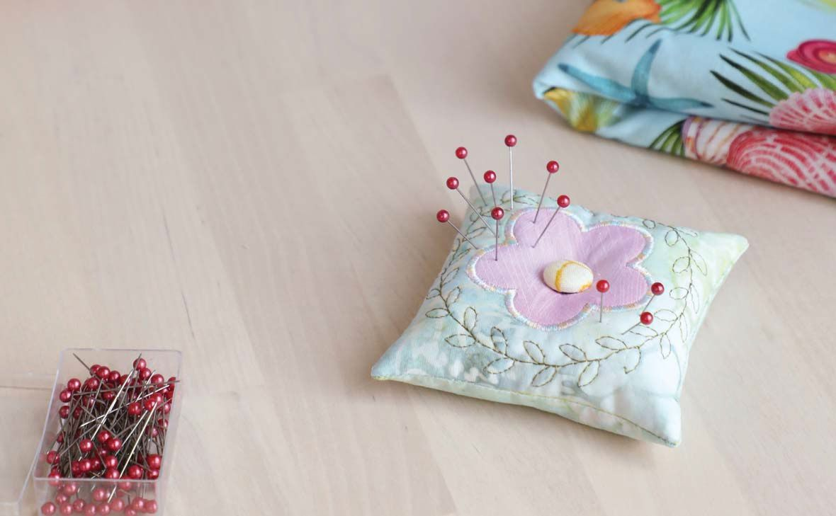 A quilted pincushion with floral applique, featured in Creative Machine Embroidery Spring 2021.