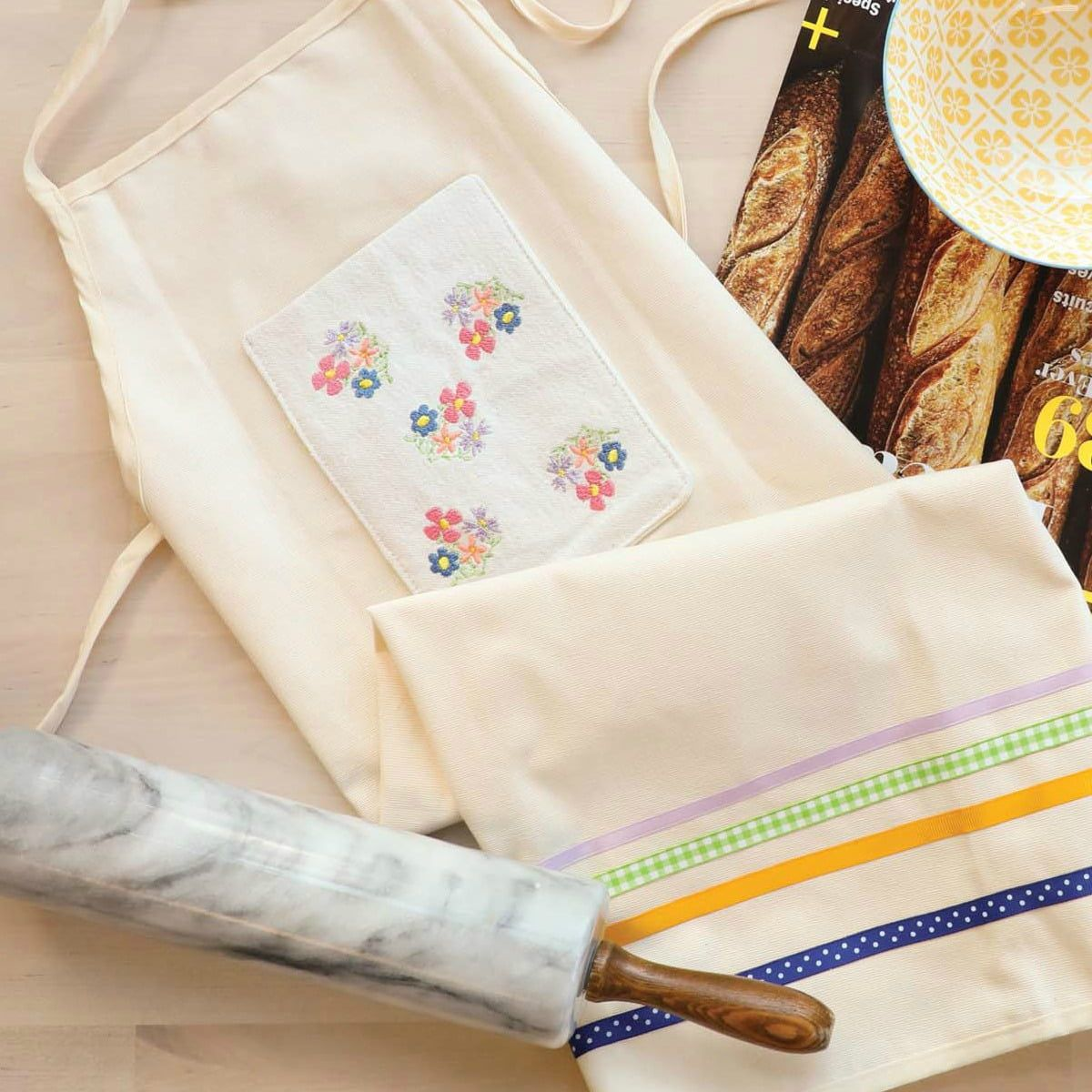 An off-white apron featuring machine-embroidered floral bunches on the front pocket, with colored ribbon trim at the bottom.